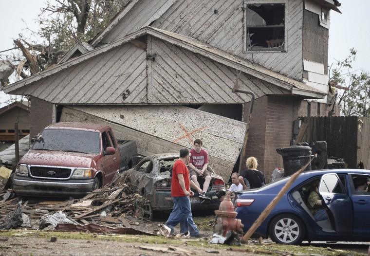 People are seen next to a damaged house and vehicles along a street after a huge tornado, in Moore, Oklahoma May 20, 2013. A 2-mile-wide (3-km-wide) tornado tore through the Oklahoma City suburb of Moore on Monday, killing at least 51 people while destroying entire tracts of homes, piling cars atop one another, and trapping two dozen school children beneath rubble. (Gene Blevins/Reuters)