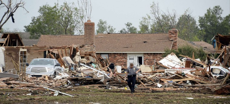 A law enforcement official stands in the yard of a damaged home after a tornado struck Moore, Oklahoma, May 20, 2013. A 2-mile-wide (3-km-wide) tornado tore through the Oklahoma City suburb of Moore on Monday. (Gene Blevins/Reuters)