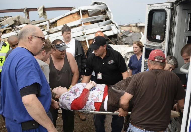 Rescue workers help one of 15 people rescued after being trap in a medical building at the Moore hospital complex after a tornado tore through the area of Moore, Oklahoma May 20, 2013. (Gene Blevins/Reuters)