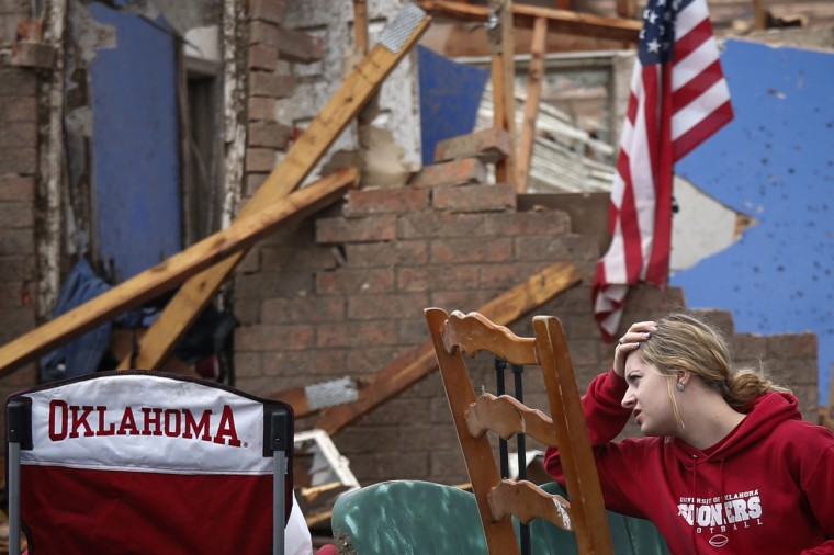 Resident Taylor Tennyson sits in the front yard of her family home which was left devastated by a tornado in Moore, Oklahoma, in the outskirts of Oklahoma City May 21, 2013. Rescuers went building to building in search of victims and thousands of survivors were homeless on Tuesday, a day after a massive tornado tore through a suburb of Oklahoma City, wiping out whole blocks of homes and killing at least 24 people. (Adrees Latif/Reuters)