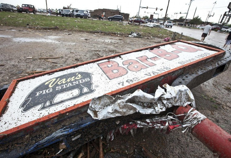 A sign for a local restaurant lies on the ground after a huge tornado struck Moore, Oklahoma, near Oklahoma City, May 20, 2013. A massive tornado tore through the Oklahoma City suburb of Moore on Monday, killing at least 51 people as winds of up to 200 miles per hour (320 kph) flattened entire tracts of homes, two schools and a hospital, leaving a wake of tangled wreckage. (Richard Rowe/Reuters)