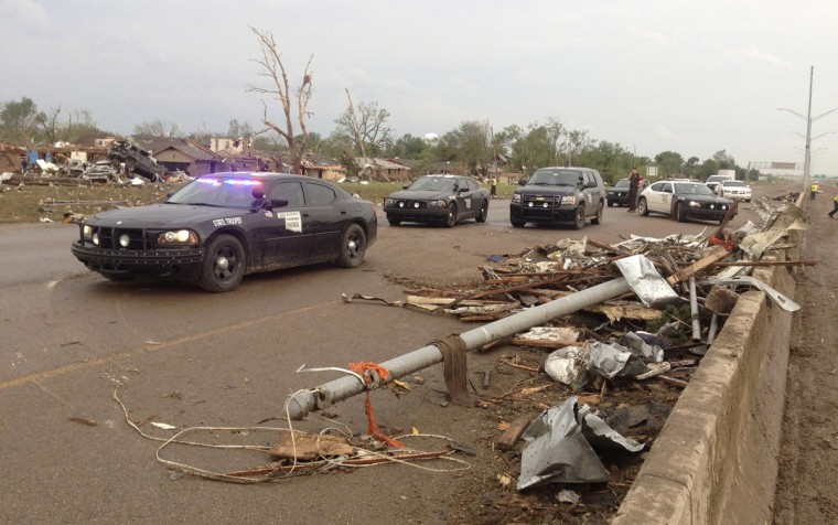 Law enforcement officials arrive on the scene after a huge tornado struck Moore, Oklahoma, near Oklahoma City, May 20, 2013. The powerful tornado that struck the town of Moore, Oklahoma, on Monday was given a preliminary rating of at least EF4, or the second highest strength level, with winds of up to 200 miles per hour (321 kph), a U.S. government agency said. (Richard Rowe/Reuters)