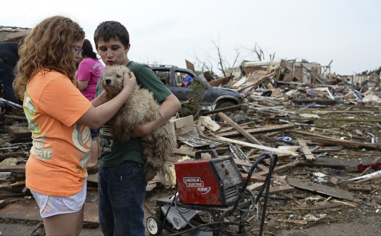Abby Madi (L) and Peterson Zatterlee comforts Zaterlee's dog Rippy, after a tornado struck Moore, Oklahoma, May 20, 2013. A 2-mile-wide (3-km-wide) tornado tore through the Oklahoma City suburb of Moore on Monday. (Gene Blevins/Reuters)