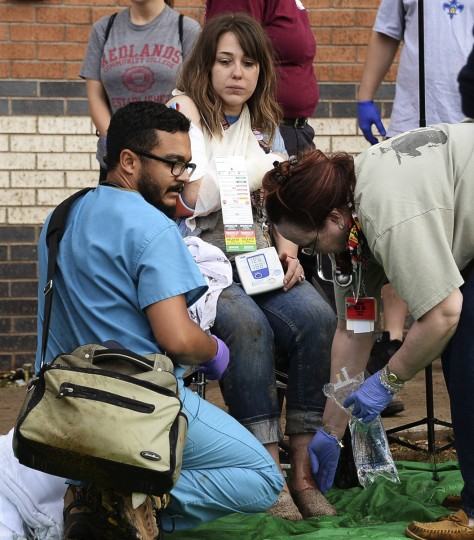 A woman is treated for her injuries at a triage area set up for the injured, after a tornado struck Moore, Oklahoma, near Oklahoma City, May 20, 2013. (Gene Blevins/Reuters)