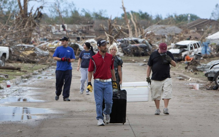 Residents remove their belongings from a residential area in Moore, Oklahoma May 21, 2013 after a massive tornado struck the area May 20. Emergency workers pulled more than 100 survivors from the rubble of homes, schools and a hospital in an Oklahoma town hit by a powerful tornado May 20, and officials lowered the death toll from the storm to 24, including nine children. (Richard Rowe/Reuters)