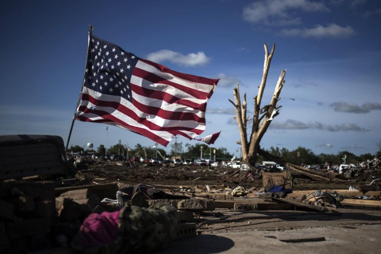 A flag is placed in the foundation of a flattened home day after a tornado devastated the town Moore, Oklahoma, on the outskirts of Oklahoma City May 21, 2013. Rescuers went building to building in search of victims and thousands of survivors were homeless on Tuesday after a massive tornado tore through the Oklahoma City suburb of Moore, wiping out whole blocks of homes and killing at least 24 people. (Adrees Latif/Reuters)