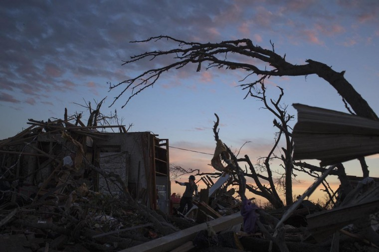 A woman searches for possessions at sunset after the suburb of Moore, Oklahoma was left devastated by a tornado, May 21, 2013. Rescuers went building to building in search of victims and survivors picked through the rubble of their shattered homes on Tuesday, a day after a massive tornado tore through the Oklahoma City suburb of Moore, wiping out blocks of houses and killing at least 24 people. (Adrees Latif/Reuters)