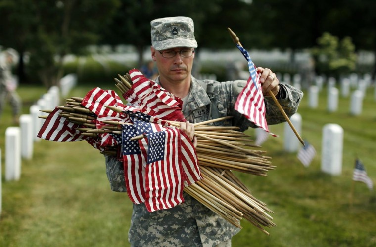 "A soldier from the Third U.S. Infantry Regiment (The Old Guard) carries flags to be placed beside graves at Arlington National Cemetery in Virginia May 23, 2013. The annual ""Flags-In"" ceremony is held ahead of Memorial Day to honor the nation's fallen members of the military. Flags will be placed at more than 220,000 graves. (Kevin Lamarque/Reuters)"
