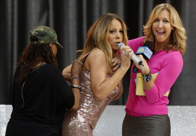 Singer Mariah Carey (C) has her dress repaired as host Lara Spencer (R) helps to hold it up on ABC's 'Good Morning America' show in New York. Carey's dress split open in the back during an interview between performances on the live broadcast of the morning show in Central Park. (Brendan McDermid/Reuters)