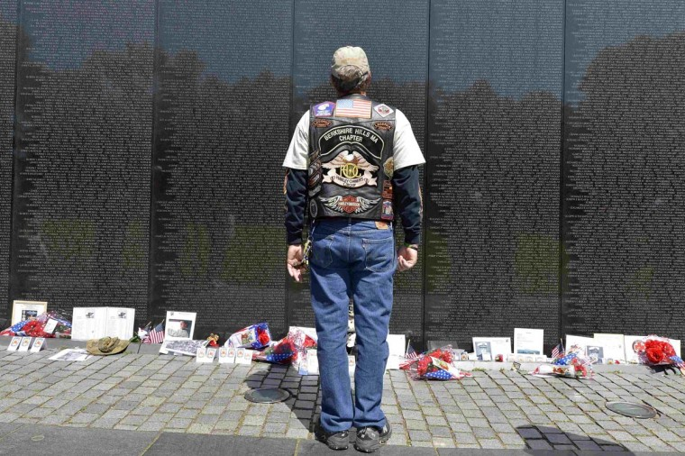 U.S. Army veteran Bob LeBlanc of Berkshire Hills, Massachusetts, stands at attention as he views the name of a fallen soldier from his hometown on the Vietnam Veterans Memorial, as he joins hundreds of thousands of motorcycle riders on Memorial Day weekend for the 26th Annual Rolling Thunder Rally to remember POWs and MIAs from America's wars, in Washington, May 26, 2013. (Mike Theiler/Reuters)