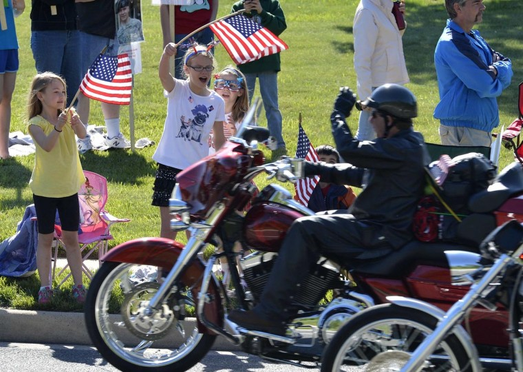 Young girls wave American flags as they cheer hundreds of thousands of motorcyclists in Fairfax, Virginia, gathering on Memorial Day weekend for the 26th Annual Rolling Thunder Rally to remember POWs and MIAs from America's wars, in Washington, May 26, 2013. (Mike Theiler/Reuters)
