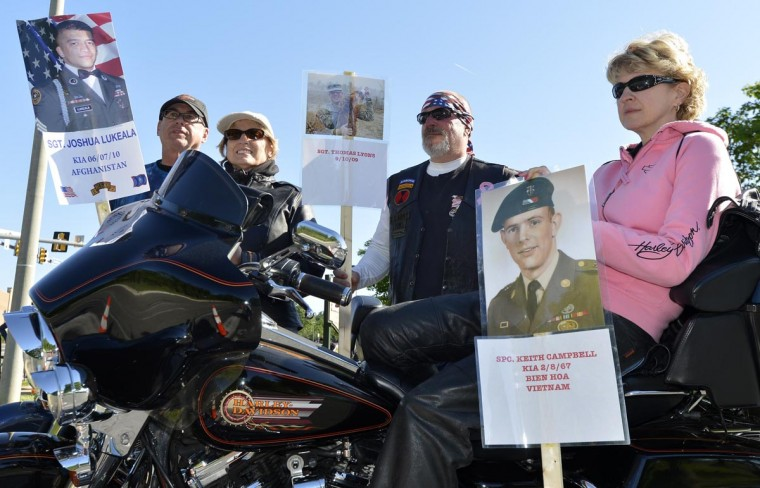 Motorcycle riders (L-R) Doug and Diane Frame and Walter and Deanna Lyons of Manassas, Virginia, hold posters of fallen U.S. military personnel as they await the arrival of hundreds of thousands of motorcyclists in Fairfax, Virginia, gathering on Memorial Day weekend for the 26th Annual Rolling Thunder Rally to remember POWs and MIAs from America's wars, in Washington, May 26, 2013. (Mike Theiler/Reuters)
