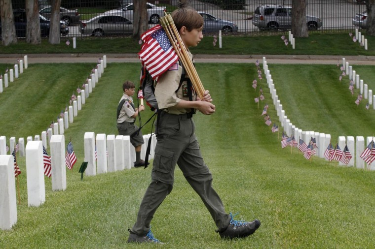 A Boy Scout walks past gravesites of U.S. military veterans at the Los Angeles National Cemetery during a flag placement event to commemorate Memorial Day weekend in Los Angeles, California, May 25, 2013. (Jonathan Alcorn/Reuters)