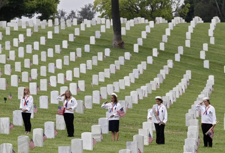 Members of a Mariner Girl Scout troop salute at gravesites of U.S. military veterans at the Los Angeles National Cemetery during a flag placement event to commemorate Memorial Day weekend in Los Angeles, California, May 25, 2013. (Jonathan Alcorn/Reuters)