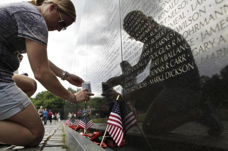 A woman takes pictures of the Vietnam Veterans Memorial wall, etched with the names of more than 58,000 U.S. servicemen and women who died in the war, in Washington May 23, 2013. Memorial Day falls on May 27 this year. (Yuri Gripas/Reuters)