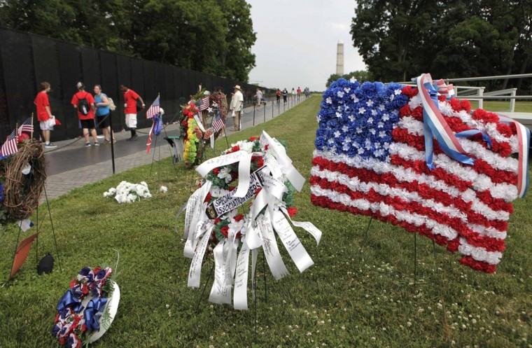 The U.S. national flag composed of flowers is placed near the Vietnam Veterans Memorial wall etched with names of more than 58,000 U.S. servicemen and women who died in the war, in Washington May 23, 2013. Memorial Day will fall on May 27 this year. (Yuri Gripas/Reuters)