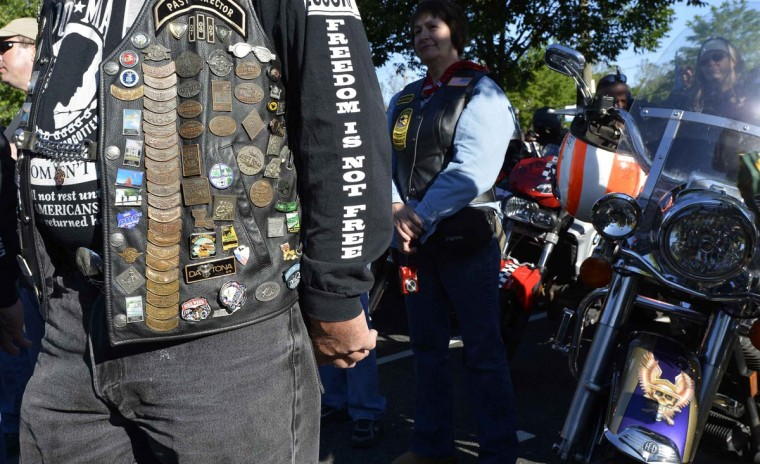 Motorcycle rider Andy Andersen of Newnan, Georgia, a Navy, Marine Corps and Air Force veteran, displays his pins and patches as he stands at attention for the playing of the National Anthem in Fairfax, Virginia, as he prepares to join hundreds of thousands of other motorcycle riders gathering on Memorial Day weekend for the 26th Annual Rolling Thunder Rally to remember POWs and MIAs from America's wars, in Washington, May 26, 2013. (Mike Theiler/Reuters)