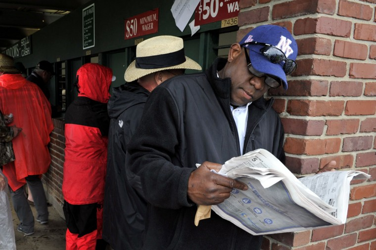 Race fan Dirk Jemmott reads a newspaper next to the betting windows before the 2013 Kentucky Derby at Churchill Downs in Louisville Kentucky. (Jamie Rhodes/USA TODAY Sports)