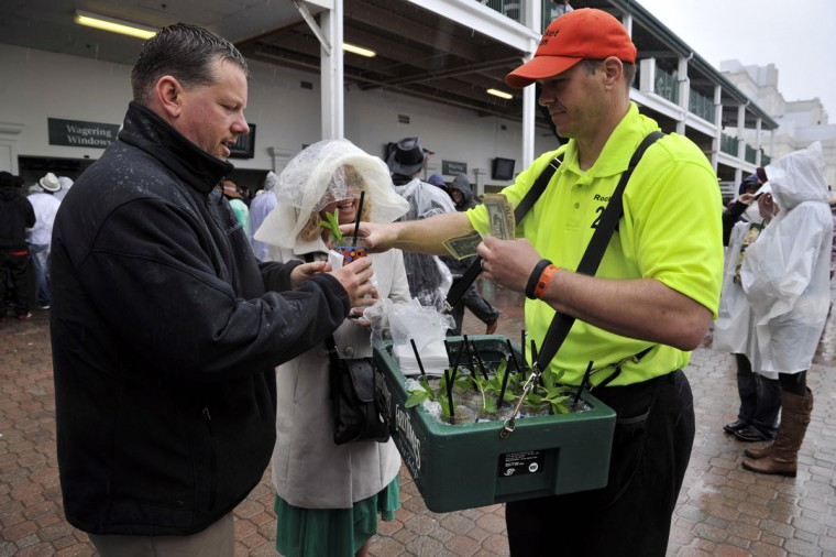 Beverage vendor Jason Kreimer (right) sells a mint julep to Adam Hazelwood (left) and Teri Hazelwood before the 2013 Kentucky Derby at Churchill Downs. (Jamie Rhodes/USA TODAY Sports)