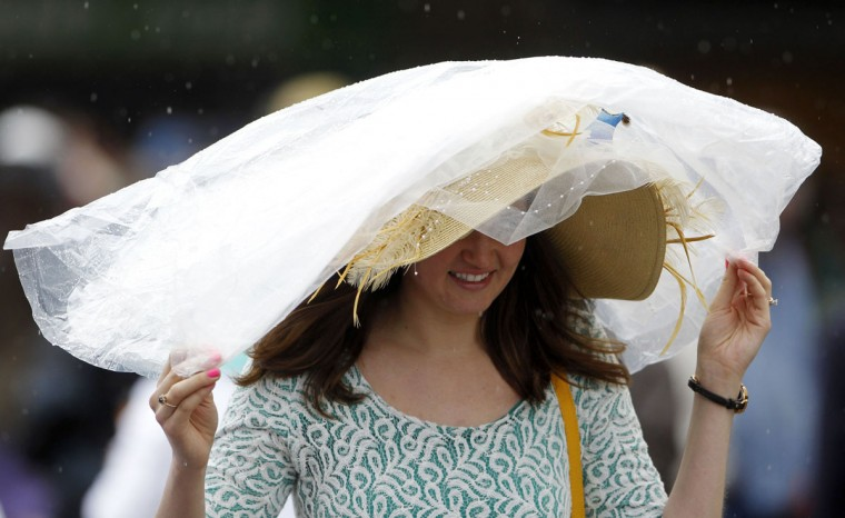 Race fan Elsha Bodily covers her Derby hat with a rain poncho before the 2013 Kentucky Derby at Churchill Downs in Louisville, Kentucky. (Mark Zerof/USATODAY Sports)