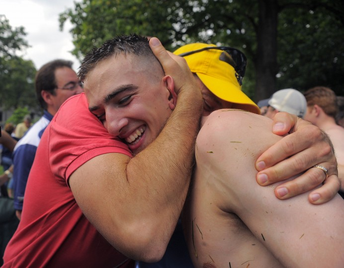 Brad Ecker of Clarence Center, NY (wearing cap) embraces his son Daniel Ecker at the conclusion of the climbing of the Herndon Monument at the U.S. Naval Academy. The event is symbolic and not mandatory; the plebes, who have become midshipmen replaced the plebe's cap with a Midshipman's cap in 1:32:43. (Karl Merton Ferron/Baltimore Sun)