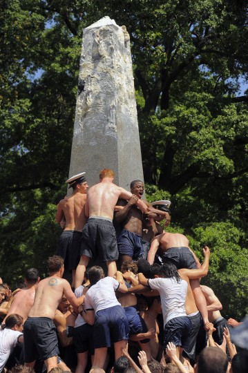 Plebes link together in the climbing of the greased Herndon Monument. (Karl Merton Ferron/Baltimore Sun)