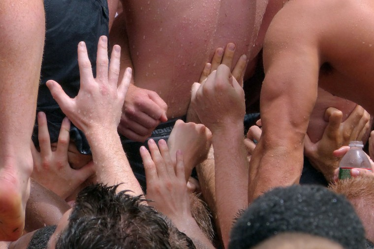 Plebes' hands reach up to help in the climbing of the monument. (Karl Merton Ferron/Baltimore Sun)