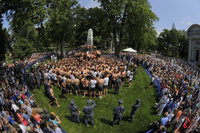 Spectators watch as the mass of bodies surround the greased obelisk during the climbing of the Herndon Monument at the U.S. Naval Academy. (Karl Merton Ferron/Baltimore Sun)