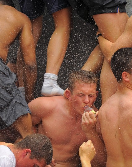 One plebe manages to take a sip of water while being stepped on and sprayed upon. (Karl Merton Ferron/Baltimore Sun)