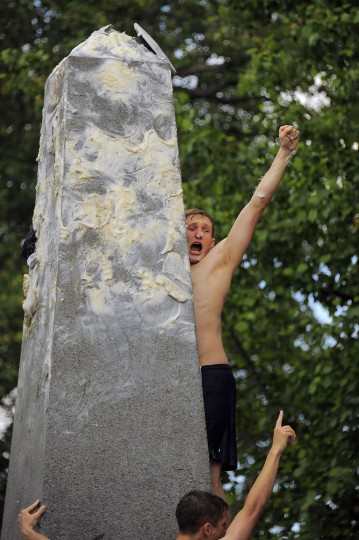 Pat Lien of Orlando, FL celebrates after tossing the Midshipmen's cap securely above, during the climbing of the greased Herndon Monument at the U.S. Naval Academy. (Karl Merton Ferron/Baltimore Sun)