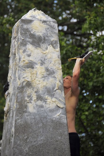 Pat Lien of Orlando, FL reaches back the Midshipmen's cap, during the climbing of the greased Herndon Monument. (Karl Merton Ferron/Baltimore Sun)