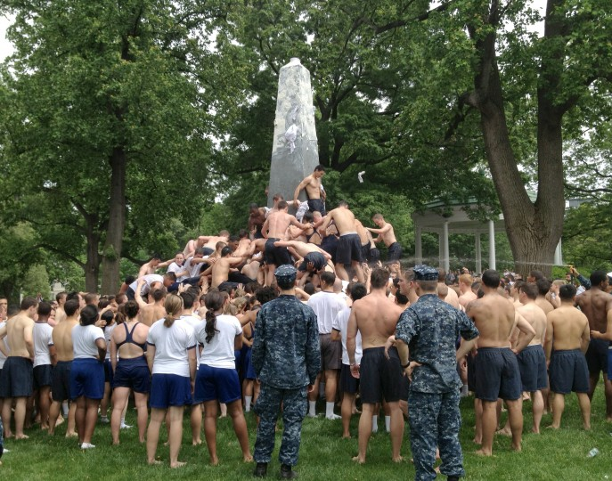 """The Naval Academy's Class of 2016's Herndon Monument climb near the front of the Naval Academy Chapel. Roughly 1,000 members of the academy's plebe (freshman) class form a human pyramid around the 21-foot tall Herndon Monument to remove a plebe hat, or """"dixie cup,"""" that upperclassmen have placed on the top of the obelisk. The midshipman who makes it to the top then replaces the """"dixie cup"""" with a midshipman's hat. (Karl Merton Ferron/Baltimore Sun)"""