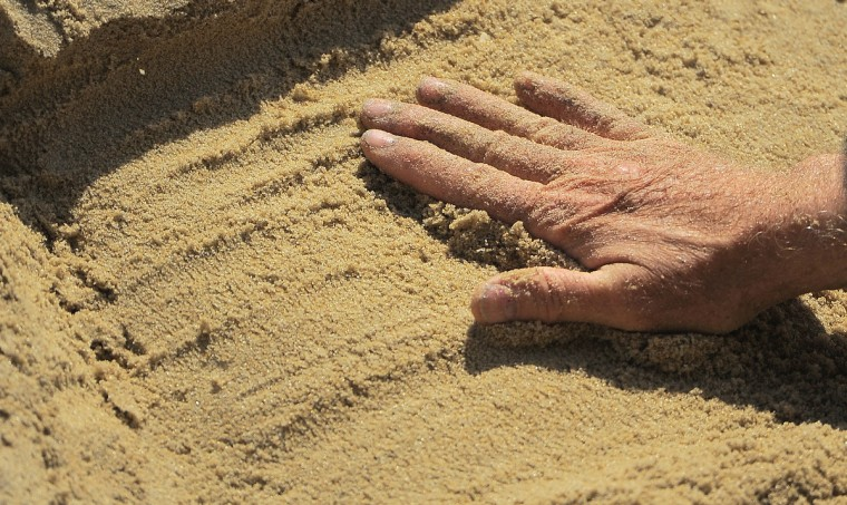Minister artist Randy Hofman manipulates the sand at the Ocean City beach, where he regularly creates biblical sand sculptures. (Karl Merton Ferron/Baltimore Sun)