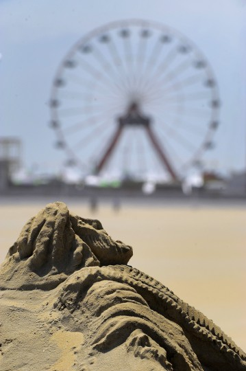 The large ferris wheel sits in the background of the sand sculpture of Jesus Christ having risen looks up, created by minister artist Randy Hofman at the Ocean City Boardwalk, where he regularly creates biblical sand sculptures. (Karl Merton Ferron/Baltimore Sun)