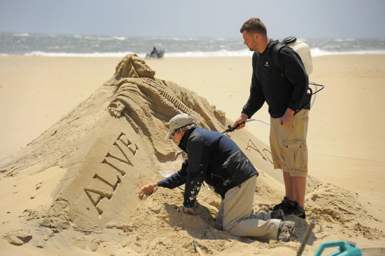 Minister artist Randy Hofman works on his knees, while Andy Deihm of Lancaster, PA, in the area for religious education, wears a container of a biodegradable glue solution on Hofman's rendering of Jesus Christ at the Ocean City Boardwalk. (Karl Merton Ferron/Baltimore Sun)