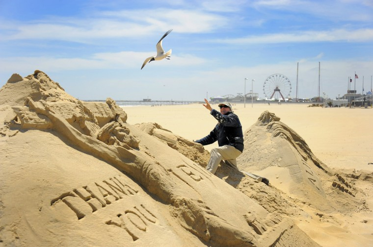 Working on the center of three sculptures, minister artist Randy Hofman pauses as a sea bird swoops from above as he creates his renderings of Jesus Christ at the Ocean City Boardwalk. (Karl Merton Ferron/Baltimore Sun)