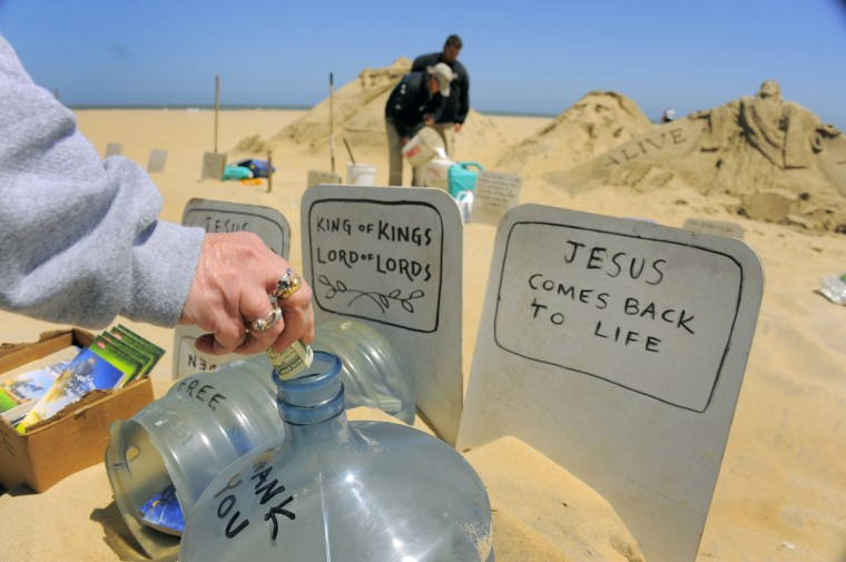 A passer-by pauses to drop money into a tip container as minister artist Randy Hofman creates his renderings of Jesus Christ, with the help of Andy Deihm of Lancaster, PA (behind), who is in the area for religious education. (Karl Merton Ferron/Baltimore Sun)