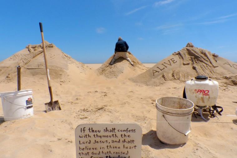 Minister artist Randy Hofman, seen working on a sand pile, regularly creates biblical sand sculptures along the Ocean City Boardwalk. (Karl Merton Ferron/Baltimore Sun)