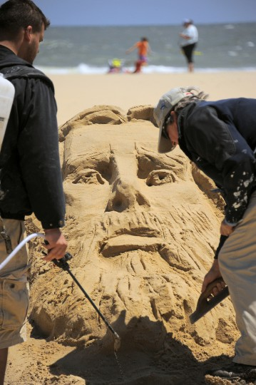 Minister artist Randy Hofman, right, continues work on one of his renderings of Jesus Christ, with the help of Andy Deihm of Lancaster, PA, who is wearing a canister pack of a biodegradable adhesive solution. (Karl Merton Ferron/Baltimore Sun)
