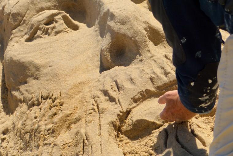 Minister artist Randy Hofman sculpts from sand the center portrait of a rendering of Jesus Christ along the Ocean City Boardwalk. (Karl Merton Ferron/Baltimore Sun)