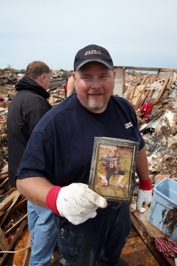Curtis Cooks recovers his high school football photo from the rubble of his house after a powerful tornado ripped through the area destroying his home on May 21, 2013 in Moore, Oklahoma. The town reported a tornado of at least EF4 strength and two miles wide that touched down yesterday killing at least 24 people and leveling everything in its path. U.S. President Barack Obama promised federal aid to supplement state and local recovery efforts. (Scott Olson/Getty Images)