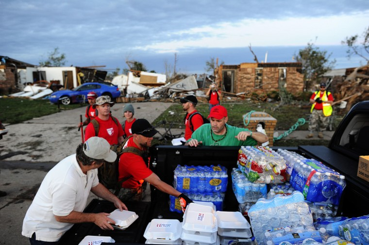 Volunteers from Mercy Chefs distribute hot food to tornado victims and rescue workers at a devastated neighbourhood on May 21, 2013 in Moore, Oklahoma. Families returned to a blasted moonscape that had been an American suburb Tuesday after a monstrous tornado tore through the outskirts of Oklahoma City, killing at least 24 people. Nine children were among the dead and entire neighborhoods vanished, with often the foundations being the only thing left of what used to be houses and cars tossed like toys and heaped in big piles.(Jewel Samad/AFP/Getty Images)