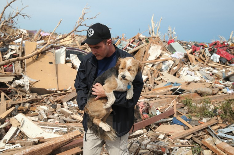 Sean Xuereb recovers a dog from the rubble of a home that was destroyed by a tornado on May 21, 2013 in Moore, Oklahoma. The town reported a tornado of at least EF4 strength and two miles wide that touched down yesterday killing at least 24 people and leveling everything in its path. U.S. President Barack Obama promised federal aid to supplement state and local recovery efforts. (Scott Olson/Getty Images)