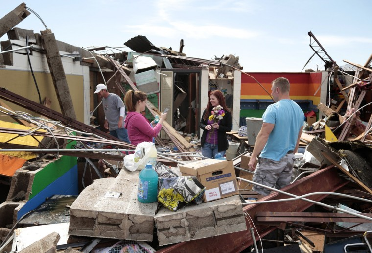Teacher's assistant Amber Ford (Left) takes a photo of first grade teacher Sheri Bittle after finding items inside Bittle's classroom at Briarwood Elementary School after the building was destroyed by yesterday's tornado on May 21, 2013 in Moore, Oklahoma. The town reported a tornado of at least EF4 strength and two miles wide that touched down yesterday killing at least 24 people and leveling everything in its path. U.S. President Barack Obama promised federal aid to supplement state and local recovery efforts. (Brett Deering/Getty Images)