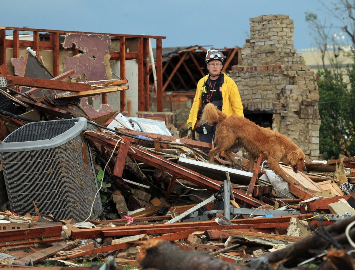 A member of Nebraska Task Force-1 looks through the remains of a home with his search dog in Moore, Oklahoma, on Tuesday, May 21, 2013. A massive tornado swept through the south Oklahoma City suburb Monday afternoon. (Brad Loper/Dallas Morning News/MCT)