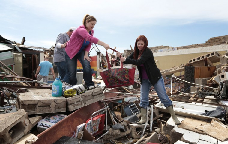 Teacher's assistant Amber Ford (Left) hands first grade teacher Sheri Bittle items found inside Bittle's classroom at Briarwood Elementary School after the building was destroyed by yesterday's tornado on May 21, 2013 in Moore, Oklahoma. The town reported a tornado of at least EF4 strength and two miles wide that touched down yesterday killing at least 24 people and leveling everything in its path. U.S. President Barack Obama promised federal aid to supplement state and local recovery efforts. (Brett Deering/Getty Images)