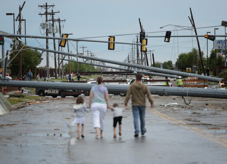 Downed utility poles block the road as a family walks south on Sante Fe Avenue at SW 19th Street after yesterday's deadly tornado on May 21, 2013 in Moore, Oklahoma. The town reported a tornado of at least EF4 strength and two miles wide that touched down yesterday killing at least 24 people and leveling everything in its path. U.S. President Barack Obama promised federal aid to supplement state and local recovery efforts. (Brett Deering/Getty Images)