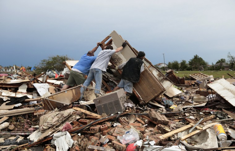 Gary Kirk, left, Billy McElrath, center, and Bill Fuller, right, look for items in the rubble of McElrath's house that was destroyed by yesterday's tornado on May 21, 2013 in Moore, Oklahoma. The town reported a tornado of at least EF4 strength and two miles wide that touched down yesterday killing at least 24 people and leveling everything in its path. U.S. President Barack Obama promised federal aid to supplement state and local recovery efforts. (Brett Deering/Getty Images)
