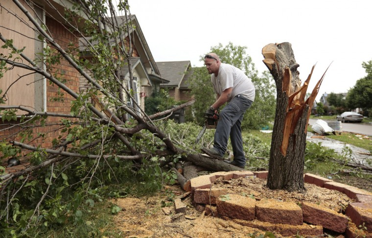 Bill Strozdas cleans up a tree in his front yard felled by yesterday's tornado on May 21, 2013 in Moore, Oklahoma. The town reported a tornado of at least EF4 strength and two miles wide that touched down yesterday killing at least 24 people and leveling everything in its path. U.S. President Barack Obama promised federal aid to supplement state and local recovery efforts. (Brett Deering/Getty Images)
