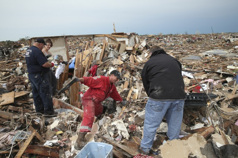 Residents search through rubble after a powerful tornado ripped through the area on May 21, 2013 in Moore, Oklahoma. The town reported a tornado of at least EF4 strength and two miles wide that touched down yesterday killing at least 24 people and leveling everything in its path. U.S. President Barack Obama promised federal aid to supplement state and local recovery efforts. (Scott Olson/Getty Images)